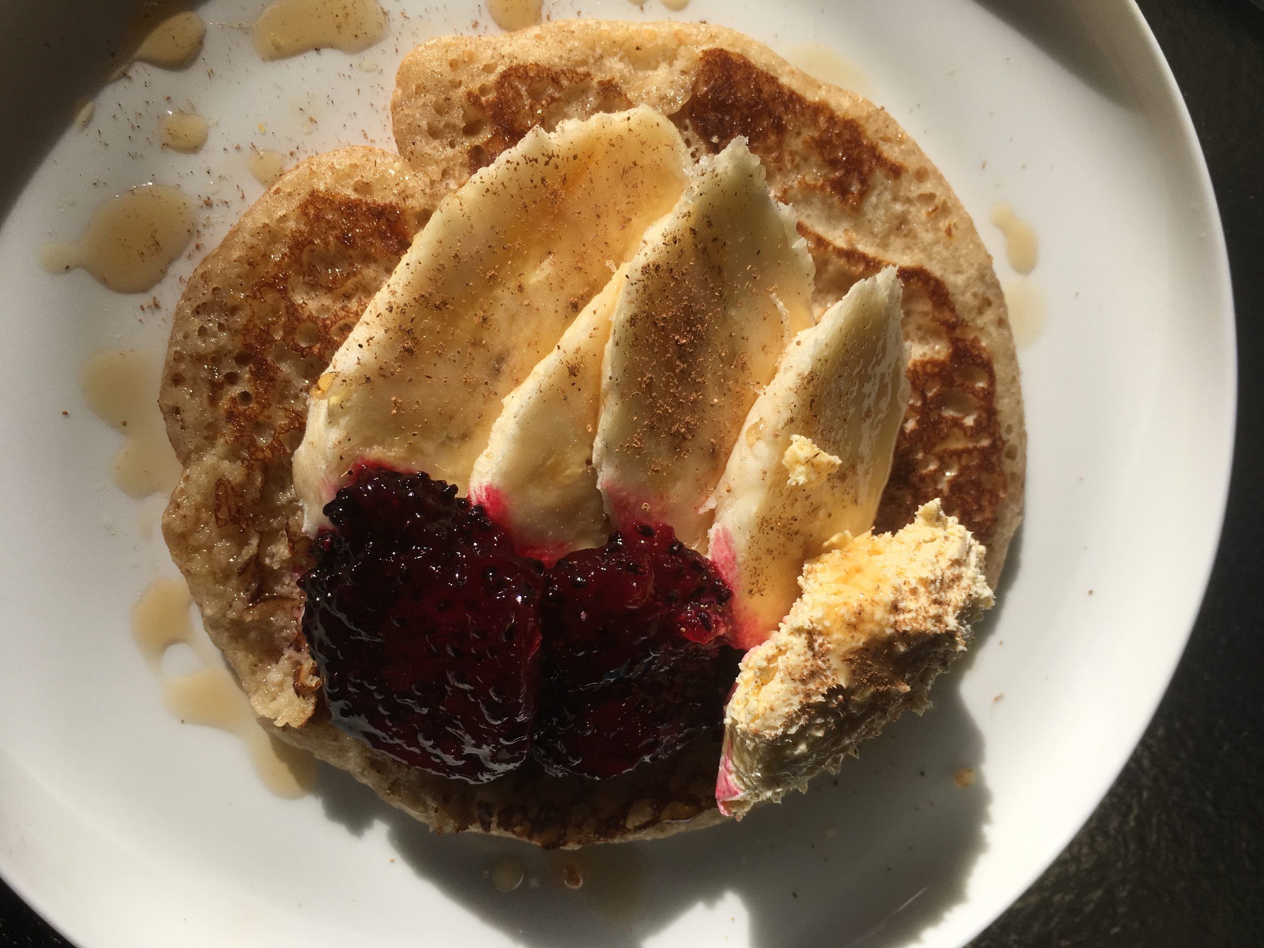 Pancakes served with sliced banana and dragon fruit with cinnamon, honey and cream